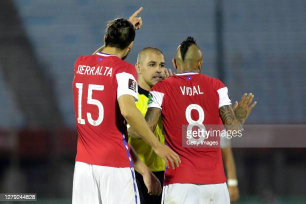 Arturo Vidal and Francisco Sierralta of Chile argue with Referee Eber Aquino Gaona during a match between Uruguay and Chile as part of South American...