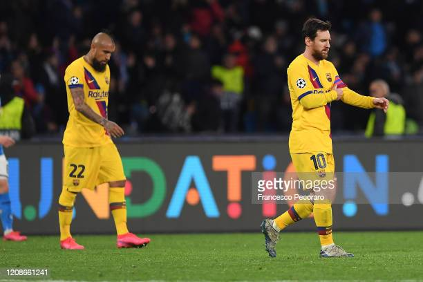 Arturo Vidal and Lionel Messi of FC Barcelona stand disappointed during the UEFA Champions League round of 16 first leg match between SSC Napoli and...