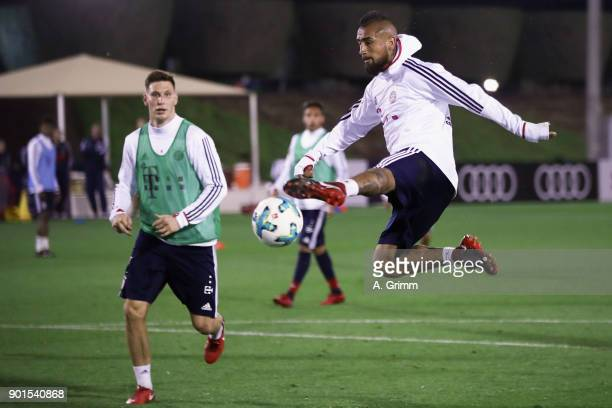 Arturo Vidal controls the ball ahead of Niklas Suele during a training session on day 4 of the FC Bayern Muenchen training camp at ASPIRE Academy for...