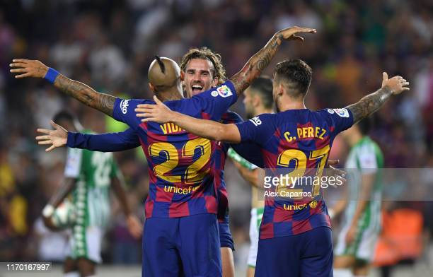 Arturo Vidal of Barcelona celebrates with teammates Antoine Griezmann and Carles Perez after scoring his team's fifth goal during the Liga match...