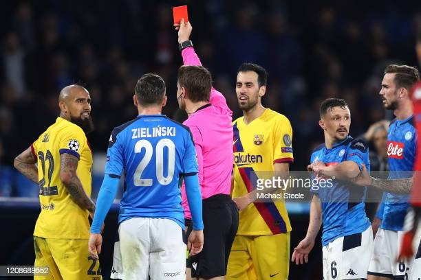 Arturo Vidal of Barcelona is shown a red card by referee Mark Borsch of Germany during the UEFA Champions League round of 16 first leg match between...
