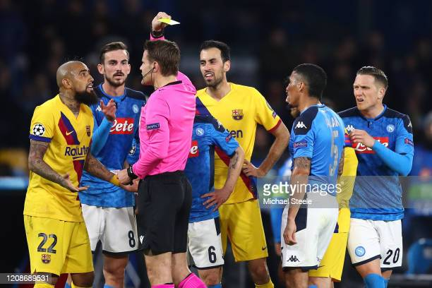 Arturo Vidal of Barcelona is shown a yellow card by referee Mark Borsch of Germany during the UEFA Champions League round of 16 first leg match...