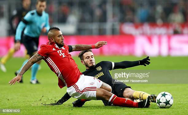 Arturo Vidal of Bayern battles for the ball with Saul Nuguez of Atletico Madrid during the UEFA Champions League match between FC Bayern Muenchen and...