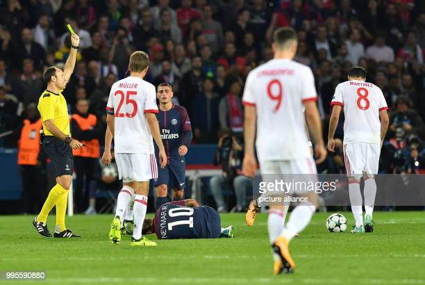 Arturo Vidal of Bayern is given a yellow card by referee Antonio Mateu Lahoz after a foul on Neymar of Paris during the Champions League football...