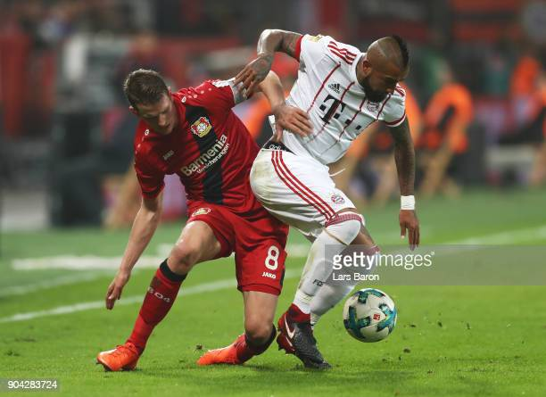 Arturo Vidal of Bayern Muenchen and Lars Bender of Bayer Leverkusen battle for the ball during the Bundesliga match between Bayer 04 Leverkusen and...