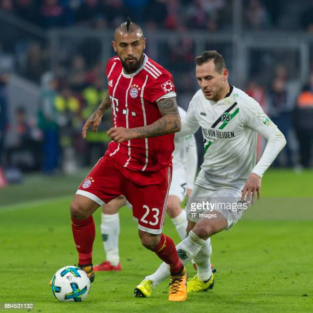Arturo Vidal of Bayern Muenchen and Marvin Bakalorz of Hannover battle for the ball during the Bundesliga match between FC Bayern Muenchen and...