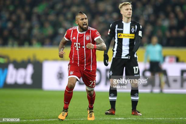 Arturo Vidal of Bayern Muenchen as Oscar Wendt of Moenchengladbach looks on celebrates after he scored a goal to make it 21 during the Bundesliga...