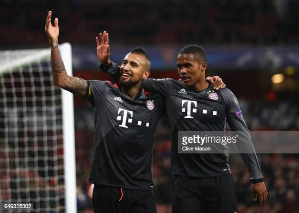 Arturo Vidal of Bayern Muenchen celebrates with Douglas Costa as he scores their fifth goal during the UEFA Champions League Round of 16 second leg...