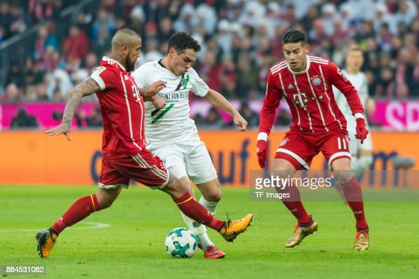 Arturo Vidal of Bayern Muenchen Manuel Schmiedebach of Hannover and James Rodriguez of Bayern Muenchen battle for the ball during the Bundesliga...