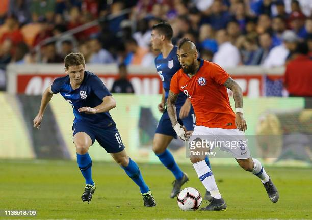 Arturo Vidal of Chile brings the ball up the pitch as Will Trapp of the USA defends in the second half at BBVA Compass Stadium on March 26, 2019 in...