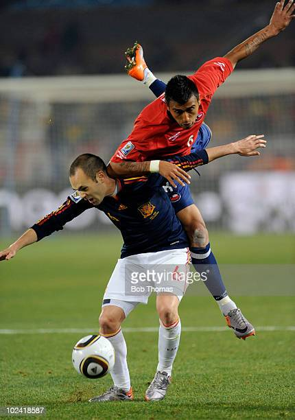 Arturo Vidal of Chile climbs over Andres Iniesta of Spain during the 2010 FIFA World Cup South Africa Group H match between Chile and Spain at Loftus...