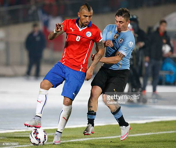 Arturo Vidal of Chile fights for the ball with Cristian Rodriguez of Uruguay during the 2015 Copa America Chile quarter final match between Chile and...