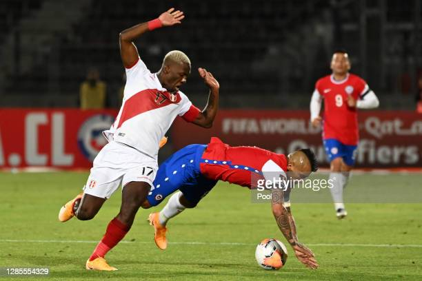 Arturo Vidal of Chile fights for the ball with Luis Advíncula of Peru during a match between Chile and Peru as part of South American Qualifiers for...