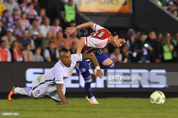 Arturo Vidal of Chile fights for the ball with Miguel Almiron of Paraguay during a match between Paraguay and Chile as part of FIFA 2018 World Cup...