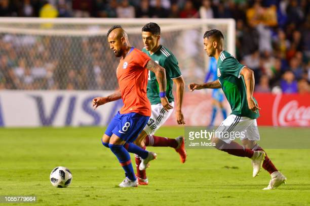Arturo Vidal of Chile fights for the ball with Raul Jimenez and Jesus Corona of Mexico during the international friendly match between Mexico and...