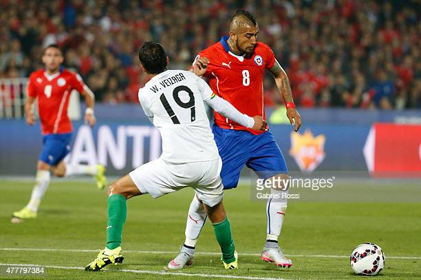 Arturo Vidal of Chile fights for the ball with Walter Veizaga of Bolivia during the 2015 Copa America Chile Group A match between Chile and Bolivia...