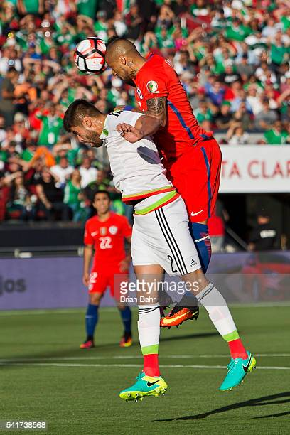 Arturo Vidal of Chile goes over Nestor Araujo of Mexico for a header in the first half of a Quarterfinal match at Levi's Stadium as part of Copa...