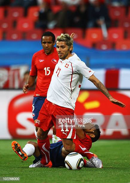 Arturo Vidal of Chile holds his face and falls to the ground following a challenge by Valon Behrami of Switzerland during the 2010 FIFA World Cup...
