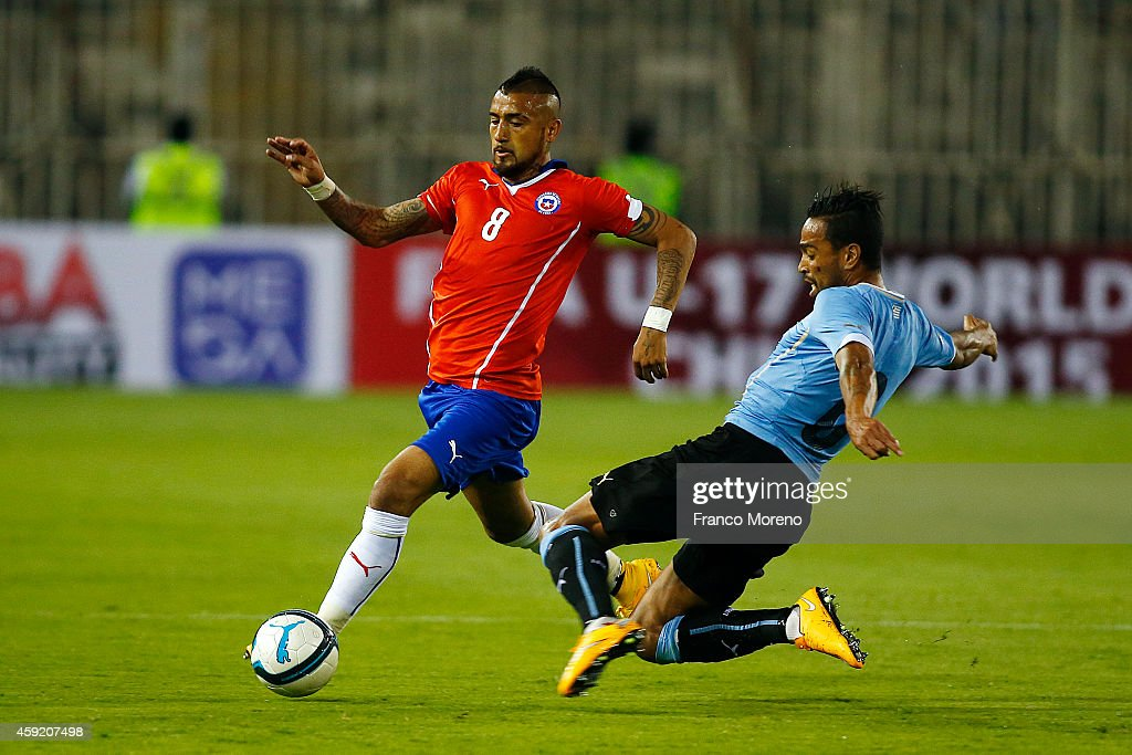Arturo Vidal of Chile (L) tries to avoid a defensive slide during an international friendly match between Chile and Uruguay at Monumental Stadium on November 18 2014 in Santiago, Chile.