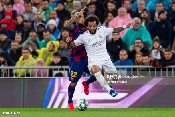Arturo Vidal of FC Barcelona and Marcelo of Real Madrid battle for the ball during the Liga match between Real Madrid CF and FC Barcelona at Estadio...