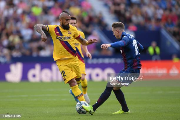 Arturo Vidal of FC Barcelona battles for possession with Carlos Clerc of Levante UD during the Liga match between Levante UD and FC Barcelona at...