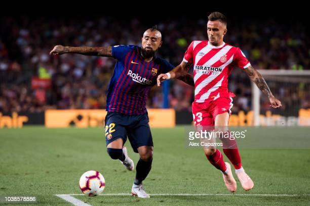 Arturo Vidal of FC Barcelona competes for the ball with Aleix Garcia of Girona FC during the La Liga match between FC Barcelona and Girona FC at Camp...