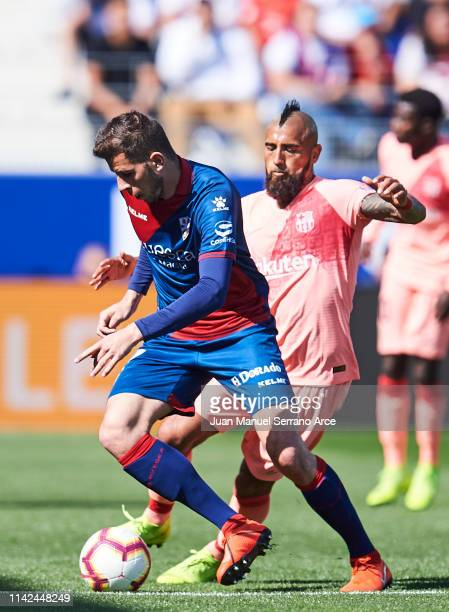 Arturo Vidal of FC Barcelona duels for the ball with Christian Rivera of SD Huesca during the La Liga match between SD Huesca and FC Barcelona at...