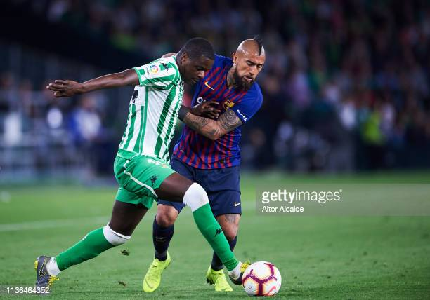 Arturo Vidal of FC Barcelona duels for the ball with William Carvalho of Real Betis Balompie during the La Liga match between Real Betis Balompie and...
