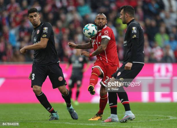 Arturo Vidal of FC Bayern Muenchen fights for the ball with Leon Balogun and Giulio Donati of Mainz 05 during the Bundesliga match between FC Bayern...
