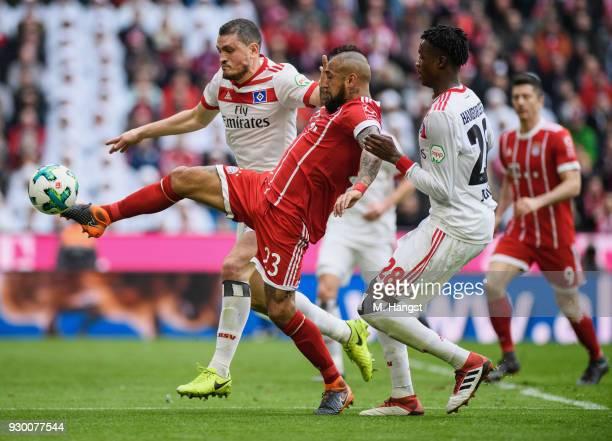 Arturo Vidal of FC Bayern Muenchen is challenged by Kyriakos Papadopoulos of Hamburg and Gideon Jung of Hamburg during the Bundesliga match between...