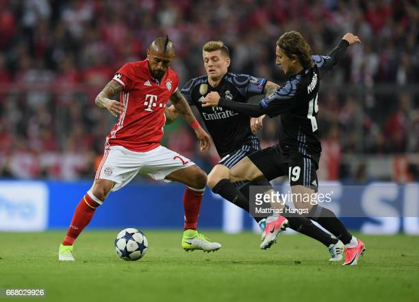 Arturo Vidal of FC Bayern Muenchen is challenged by Toni Kross of Real Madrid and Luka Modric of Real Madrid during the UEFA Champions League Quarter...