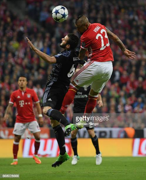 Arturo Vidal of FC Bayern Muenchen jumps for a header with Nacho of Real Madrid during the UEFA Champions League Quarter Final first leg match...