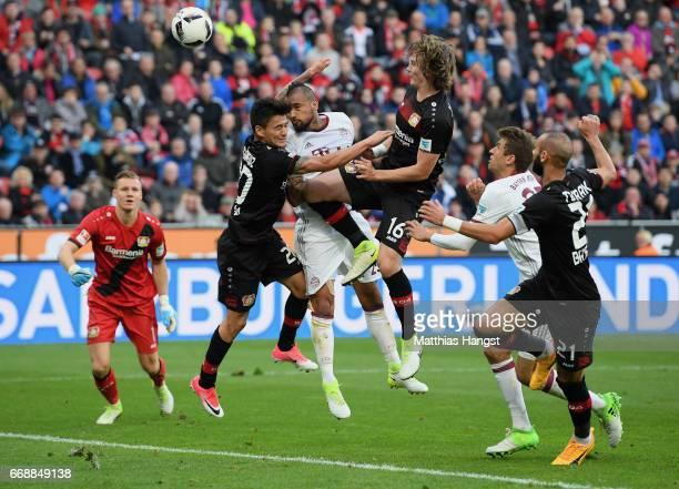 Arturo Vidal of FC Bayern Muenchen misses to score against Charles Aranguiz of Leverkusen and Tin Jedvaj of Leverkusen during the Bundesliga match...