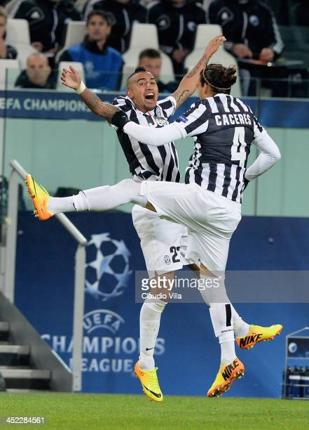 Arturo Vidal of Juventus celebrates his third goal with teammate Martin Caceres during the UEFA Champions League Group B match between Juventus and...