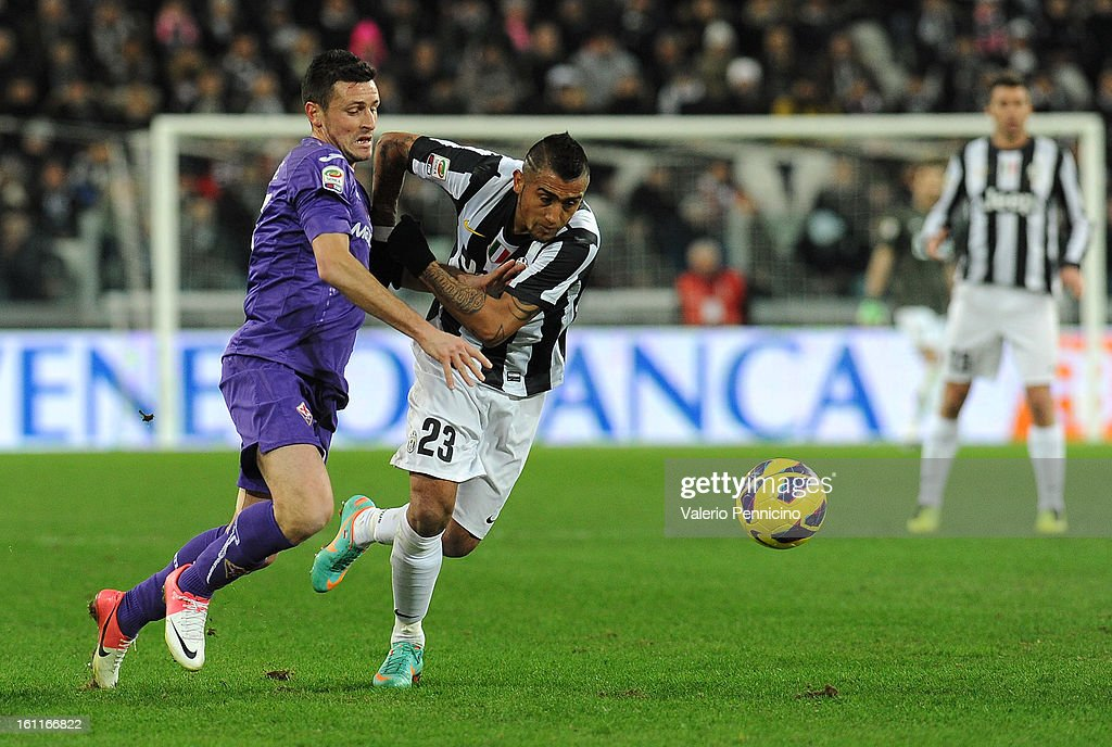 Arturo Vidal (R) of Juventus FC competes with Manuel Pasqual of ACF Fiorentina during the Serie A match between Juventus FC and ACF Fiorentina at Juventus Arena on February 9, 2013 in Turin, Italy.