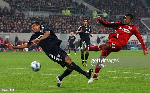 Arturo Vidal of Leverkusen shoots on goal as Lucio of Bayern defends during the DFB Cup quarter final match between Bayer 04 Leverkusen and Bayern...