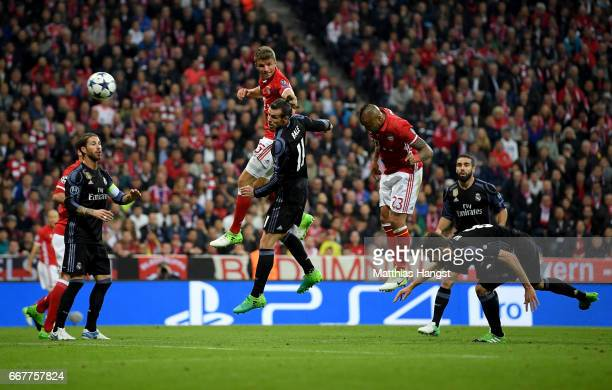 Arturo Vidal of Muenchen heads his team's opening goal during the UEFA Champions League Quarter Final first leg match between FC Bayern Muenchen and...
