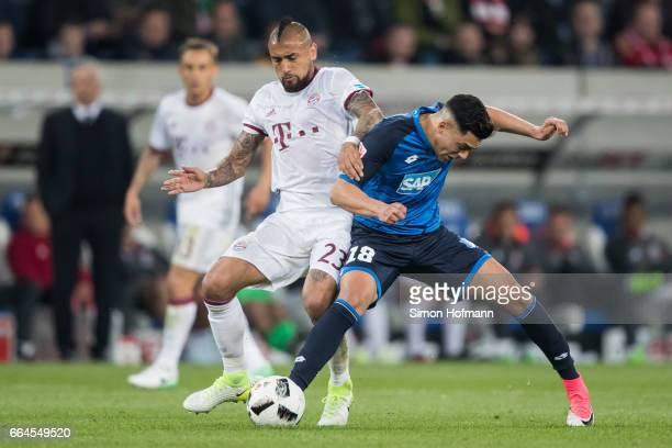 Arturo Vidal of Muenchen is challenged by Nadiem Amiri of Hoffenheim during the Bundesliga match between TSG 1899 Hoffenheim and Bayern Muenchen at...