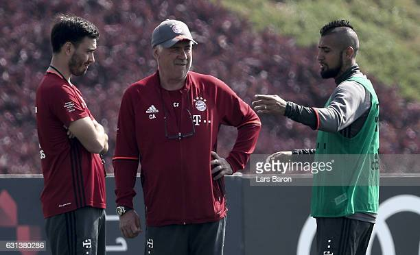 Arturo Vidal speaks to assistant coach Davide Ancelotti and head coach Carlo Ancelotti during a training session at day 8 of the Bayern Muenchen...