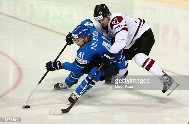 Arturs Kulda of Latvia and Antti Pihlstrom of Finland battle for the puck during the IIHF World Championship group H match between Latvia and Finland...