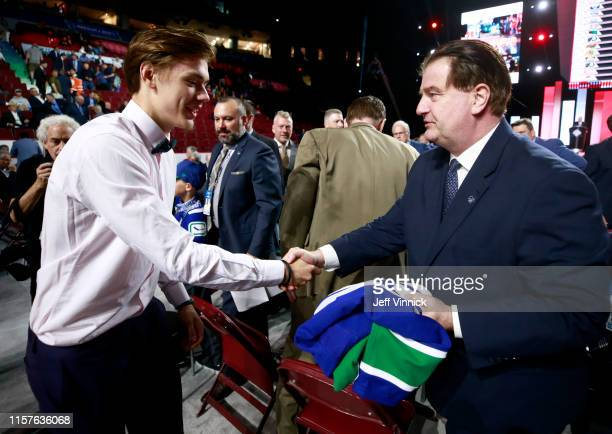 Arturs Silovs 156th pick overall of the Vancouver Canucks is greeted by general manager Jim Benning of the Vancouver Canucks on the draft floor...