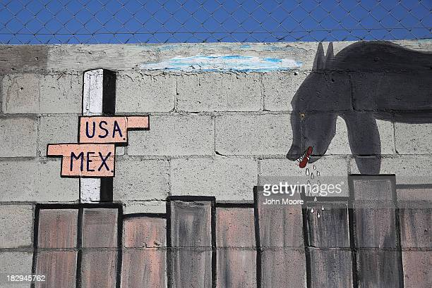 Artwork adorns the Mexican side of a wall on the US Mexico border on October 2 2013 in Tijuana Mexico Despite the US federal shutdown most border...