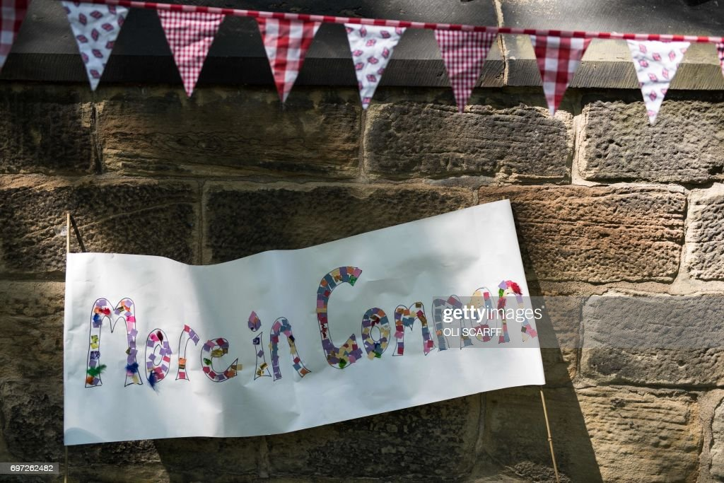 Artwork bearing a quote from murdered Member of Parliament Jo Cox is displayed at a 'Great Get Together' community service and picnic in memory of murdered Member of Parliament Jo Cox, marking the first anniversary since her killing, in the grounds of All Saints Church in Batley, northern England on June 18, 2017. The Great Get Together weekend is Inspired by murdered Labour MP Jo Cox's belief that we have more in common than which divides us, a line from her first speech to Parliament, and is a community initiative designed to unite people and communities on the streets and parks of their neighbourhoods. The 41 year-old Labour Party MP, Jo Cox, was assassinated by a pro-Nazi sympathiser in a terror attack in her constituency in northern England on June 16, 2016. /