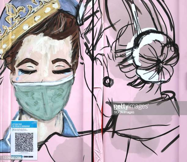 Artwork showing lady wearing a face mask in Carnaby Street. Coronavirus restriction signs and reminders are seen around London as the capital has...
