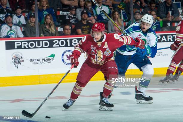 Artyom Minulin of Swift Current Broncos back checks Antoine Morand of AcadieBathurst Titan as he skates with the puck during the second period at the...