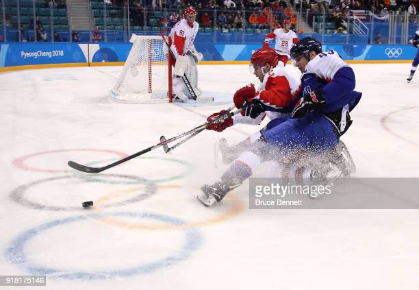 Artyom Zub of Olympic Athlete from Russia and Tomas Surovy of Slovakia compete for the puck during the Men's Ice Hockey Preliminary Round Group B...