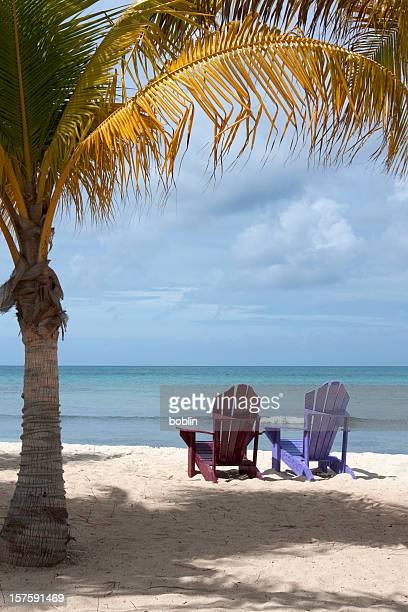 Aruban beach with two adirondack chairs under palm