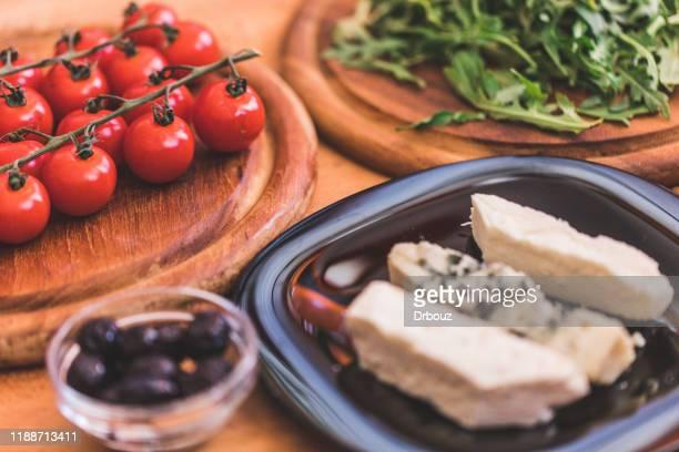 rucola en cherry tomaten met kaas salade maken, ingrediënten op tafel - blauwschimmelkaas stockfoto's en -beelden
