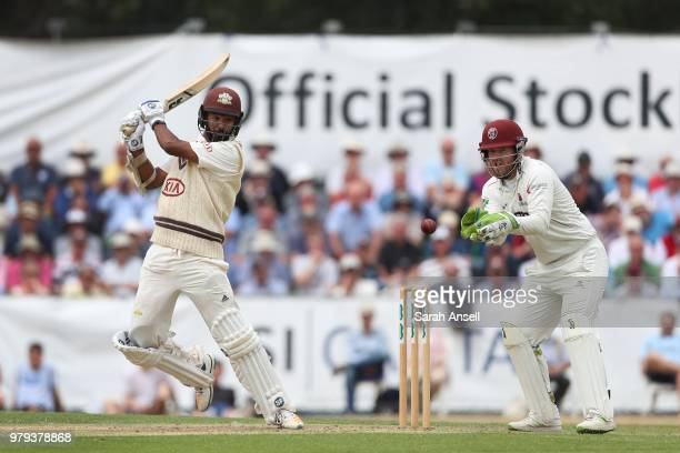 Arun Harinath of Surrey hits a boundary as Somerset wicket keeper Steven Davies during day 1 of the Specsavers County Championship Division One match...