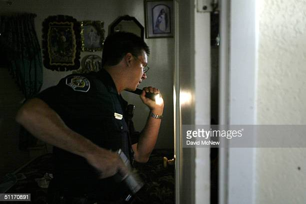 Arvin police officer Phil Bebabides draws his gun upon finding a man hiding behind a door in a house from which a 911 call was placed but no one...